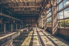 Övergett industriellt kusligt lager inom gammal mörk grungefabriksbyggnad arkivbilder