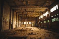 Övergett industriellt kusligt lager inom gammal mörk grungefabriksbyggnad royaltyfri foto
