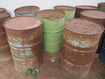 Övergett korrodera rostiga olje- trummor på jordningen Royaltyfri Foto