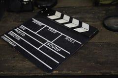 Övergett kritisera filmen eller filmclapperen på den smutsiga trätabellen royaltyfria foton