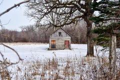 Övergett lantbrukarhem i ridit ut trä i ett snöig fält Royaltyfri Bild