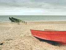 Övergett rött skovelfartyg på den sandiga stranden av havet Slät vattennivå royaltyfri foto