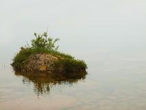Övergiven ö i sjön Stor stensi som ut klibbar från kall nivå Arkivbild