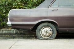 Övergiven bil med det plana gummihjulet Arkivbilder