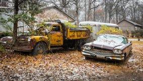 Övergiven bil och lastbilar som rostar i gård royaltyfri fotografi