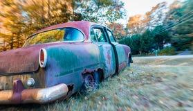 Övergiven bil som rostar i ett fält Royaltyfri Bild