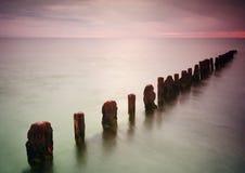 Övergiven brygga på vatten för havssolnedgång- och himmelreflexion Fotografering för Bildbyråer