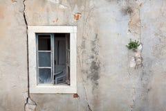Övergiven byggnad med spruckna väggar och det öppna fönstret Fotografering för Bildbyråer