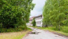 Övergiven byggnad och en väg Royaltyfri Foto