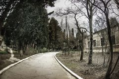 Övergiven byhusbyggnad i den Baku Botanical trädgården Inget i parkera med träd Vår arkivfoto