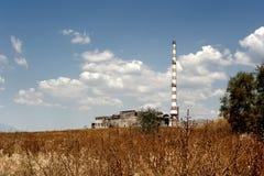 Övergiven fabrik i dramatiskt landskap Arkivbild
