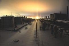 Övergiven fabrik, i vinter, med trummor och rör på de glödande ljusindustriområdena för horisont, nattlandskap arkivfoto