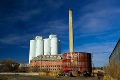 Övergiven fabrik med lagringsbehållare, fabriksskorsten och en åkerbruk silo för kornhiss i bakgrunden Royaltyfria Foton