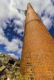 Övergiven fabrik med tegelstenfabriksskorsten och kvarlevorna av kraftverkdroppen Arkivfoton