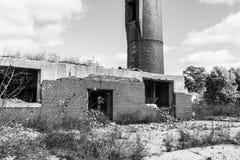 Övergiven fabrik med tegelstenfabriksskorsten och kvarlevorna av kraftverket II Arkivbild