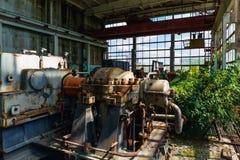 Övergiven fabrik som är bevuxen med gröna växter, rostiga maskiner och utrustning Royaltyfria Foton