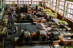 Övergiven fabrik som är bevuxen med växter Royaltyfria Bilder