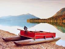 Övergiven fiskebåt på banken av fjälläng sjön Höstlig morgon på sjön Arkivbild