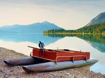 Övergiven fiskebåt på banken av fjälläng sjön Höstlig morgon på sjön Arkivbilder