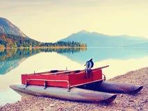 Övergiven fiskebåt på banken av fjälläng sjön Höstlig morgon på sjön Royaltyfria Foton