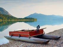 Övergiven fiskebåt på banken av fjälläng sjön Höstlig morgon på sjön Royaltyfri Bild