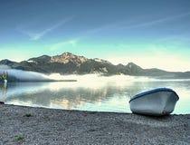 Övergiven fiskebåt på banken av fjälläng sjön Morgon lake Royaltyfri Fotografi