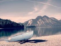 Övergiven fiskebåt på banken av fjälläng sjön Morgon lake Arkivbild