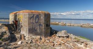 Övergiven fortbunker bredvid vatten arkivfoto