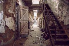 Övergiven gångbana för fängelsecell med gamla rostiga trappa, dörrar och skalningsväggar Arkivfoton
