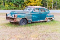 Övergiven gammal bil som förfaller i mitt av en äng Royaltyfri Foto