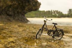 Övergiven gammal cykel under klippan arkivfoton