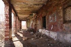Övergiven gammal fabrik med tegelstenkolonner och skräp Arkivbild