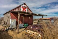 Övergiven gammal pickup framme av den öde Texaco stationen, avlägsen del av Nebraska Royaltyfria Foton