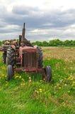 Övergiven gammal röd lantgårdtraktor i äng Arkivfoton