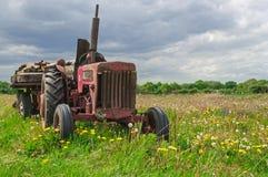 Övergiven gammal röd lantgårdtraktor i äng Fotografering för Bildbyråer