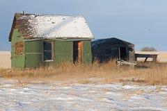 Övergiven gammal skjul och lantgårdmaskin i vinter Arkivbilder