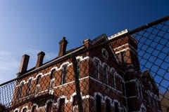 Övergiven historisk skola med röd tegelsten och vitkalkstenöverstycken Royaltyfria Bilder