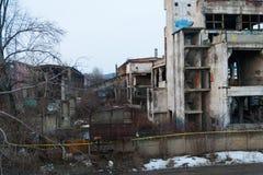 Övergiven industribyggnad med vegetation och grafitti royaltyfri foto