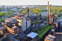 Övergiven järnverkfabrik med träd och stad i bakgrunden Arkivfoto