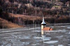 Övergiven kyrka i en gyttjasjö. Naturlig bryta katastrof med wat arkivbild