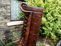 Övergiven lädersoffa i trädgård Royaltyfri Foto