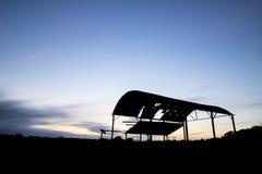Övergiven ladugårdkontur mot härlig vibrerande solnedgånglandsc Royaltyfri Fotografi
