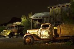Övergiven lastbil och skolbuss i spökstad Royaltyfri Foto