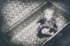 Övergiven leksak i en gammal tom resväska Arkivbild