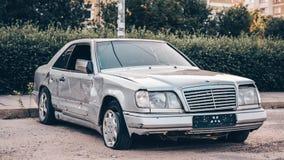 Övergiven silverbil på vägen, bilskräp Bruten och skrynklig biltransport är på gatan royaltyfri fotografi