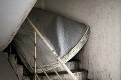 Övergiven smutsig madrass som från under blockerar den nedfläckade trappan fotografering för bildbyråer
