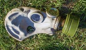 Övergiven sovjetisk gasmask på gräset i sol Arkivbilder