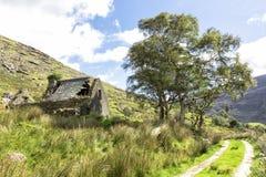Övergiven stuga och berg som fotvandrar slingan Arkivbilder