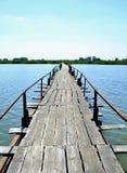 Övergiven trälång bro över sjön Arkivbild