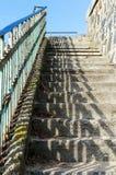 Övergiven trappuppgång med betong som kliver stenar och metallledstänger som är upplysta vid solen Royaltyfri Bild